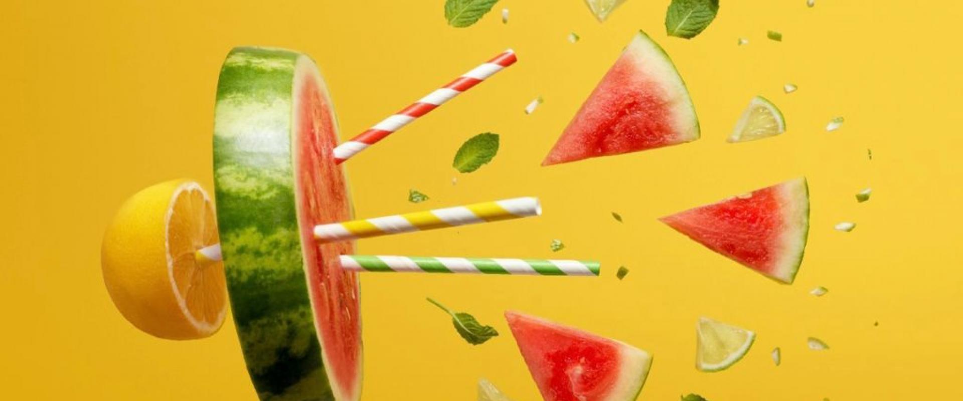 Pedacos de frutas como laranja melancia com hortela e canudos sobre fundo amarelo